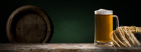 Beer in mug on wooden table near brick wall Stock Photo