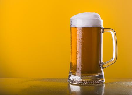 frothy: Light beer mug against the backdrop of the bar shelf