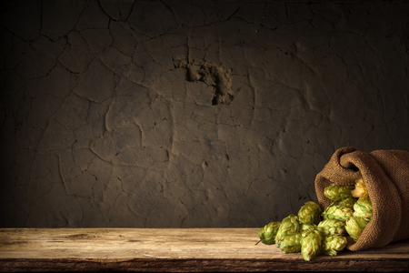 blurred background of brown barrels and hop in basket.
