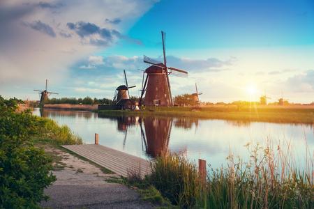 Warme en bewolkte zonsondergang op de Kinderdijk, UNESCO-werelderfgoed, Alblasserdam, Nederland Stockfoto