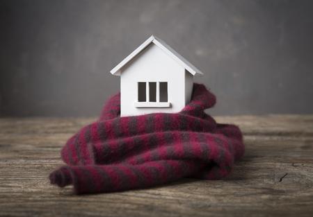 Dom zimą - koncepcja systemu grzewczego i zimna śnieżna pogoda z modelem domu w czapce z dzianiny