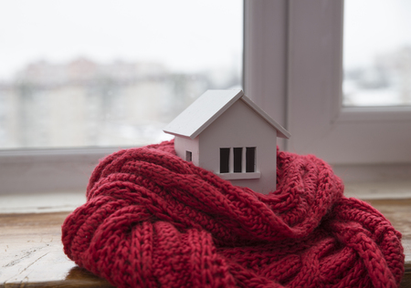 house in winter - heating system concept and cold snowy weather with model of a house wearing a knitted cap Stok Fotoğraf