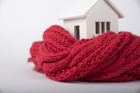 House in winter - heating system concept and cold snowy weather with model of a house wearing a knitted cap Banque d'images