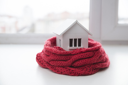house in winter - heating system concept and cold snowy weather with model of a house wearing a knitted cap Stockfoto