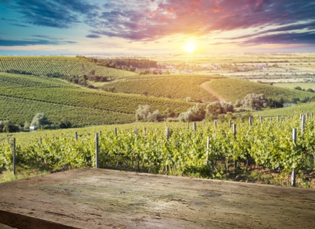 vineyard at sunset in the Chianti region in Italy and table of wood space