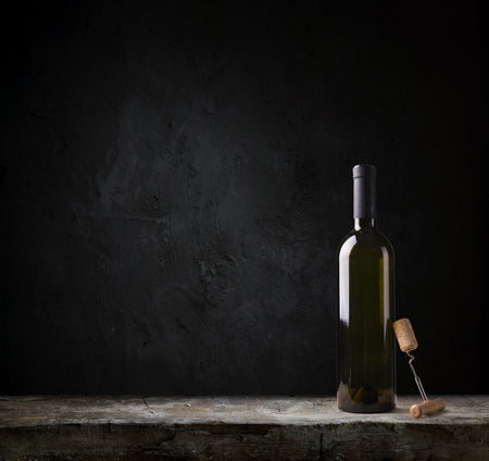 Excellent red wine bottles, wineglass, barrel and corkscrew on a rustic wooden table: traditional winemaking and wine tasting concept