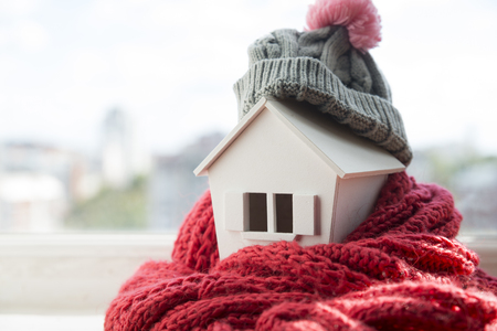 house in winter - heating system concept and cold snowy weather with model of a house wearing a knitted cap Foto de archivo