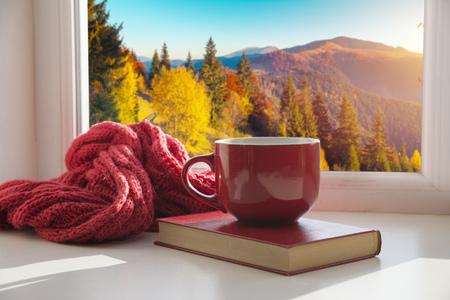 finestra con foglie d'autunno, un libro, una tazza di tè