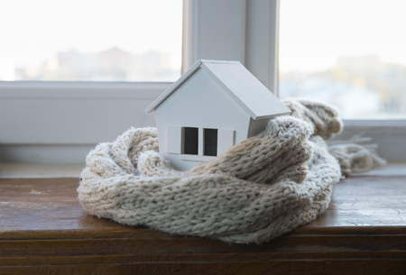 house in winter - heating system concept and cold snowy weather with model of a house wearing a knitted cap 版權商用圖片
