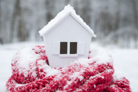 house in winter - heating system concept and cold snowy weather with model of a house wearing a knitted cap Standard-Bild