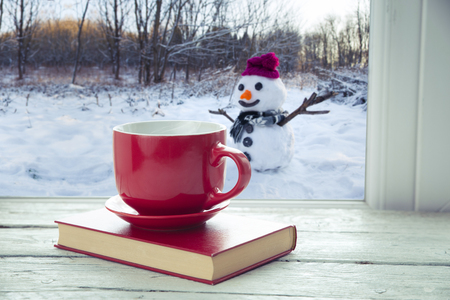 Cup of coffee on the window sill. In the background, a beautiful winter landscape in snow. Cozy home concept 免版税图像