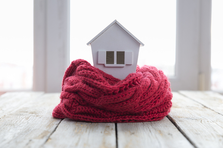 house in winter - heating system concept and cold snowy weather with model of a house wearing a knitted cap 免版税图像
