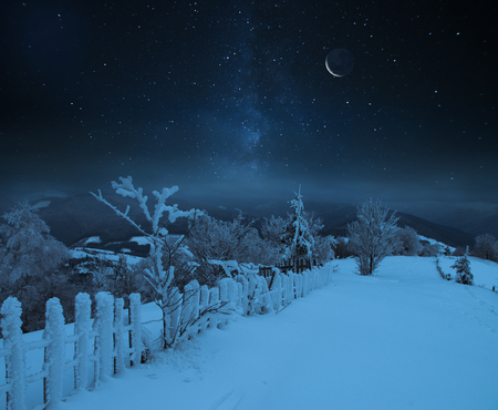 Fairy-tale starry night in the Ukrainian Carpathian mountains with the galaxy Milky way in the sky and the glow of the full moon Winter frosty time on the background of a cozy little house.