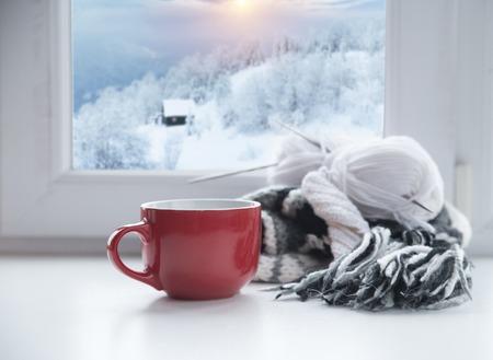 Winterachtergrond - beker met snoepriet, wollen sjaal en handschoenen op vensterbank en winters tafereel buitenshuis. Stilleven met concept om de winter door te brengen in een gezellig huis met koud weer buitenshuis