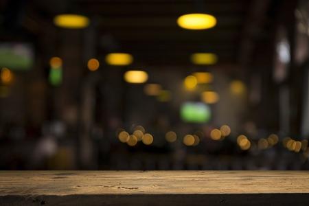 Image de table en bois en face de l'arrière-plan flou abstrait des lumières du restaurant