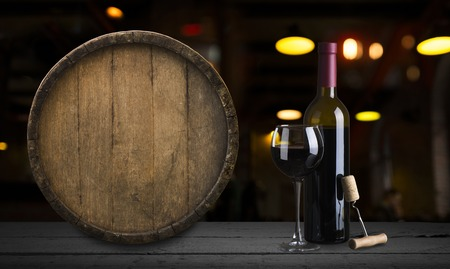 Expensive wine bottles collection and wooden barrel in the cellar, wine tasting and production concept Reklamní fotografie