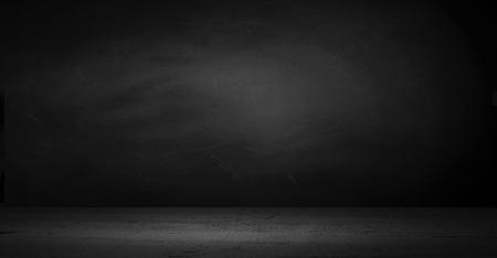Piso de cemento en cuarto oscuro con foco de luz. fondo negro.