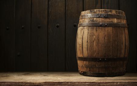 Holzfass und Bierglas auf einem alten Eichentisch aus Holz.