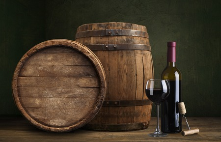 Botella y copa de vino tinto en barril de madera rodada con fondo de madera oscura.