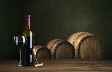 Bottiglia e bicchiere di vino rosso sul barilotto di legno girato con fondo di legno scuro