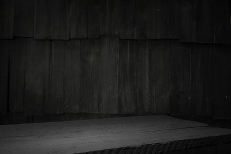 Alter Holztisch mit verschwommener Betonblockwand im dunklen Raumhintergrund. Standard-Bild
