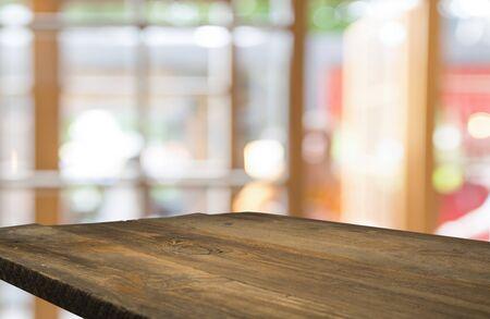 Leere Holztischplatte auf Unschärfe des Vorhangs mit Fensteransicht grün vom Baumgartenhintergrund. Für die Montage von Produktanzeigen oder das Design von Key Visual Layout