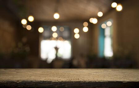 Empty wood table top on blur light gold bokeh of cafe restaurant in dark background. Stock Photo