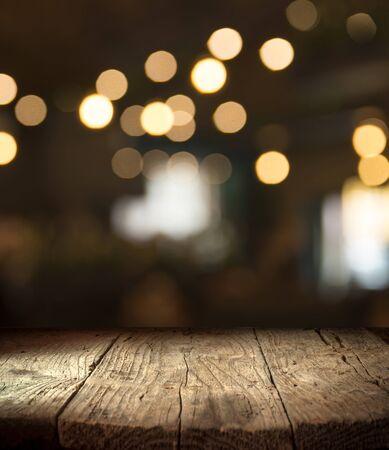 sfondo sfocato del bar e spazio sulla scrivania marrone scuro di legno retrò