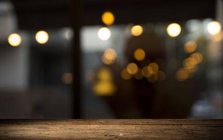 Leeg houten tafelblad op vervaging licht gouden bokeh van café-restaurant in donkere achtergrond Stockfoto