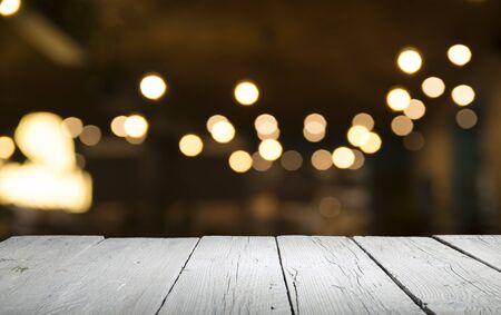 Leere Holztischplatte auf unscharfem hellgoldenem Bokeh des Café-Restaurants im dunklen Hintergrund