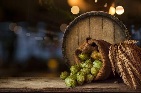 Ingrediënten voor het brouwen van bier Hop in zak en tarweoren op houten gebarsten oude tafel. Bierbrouwerijconcept. Hopbellen en tarwe close-up. Zak van hop en schoof van tarwe op vintage achtergrond.