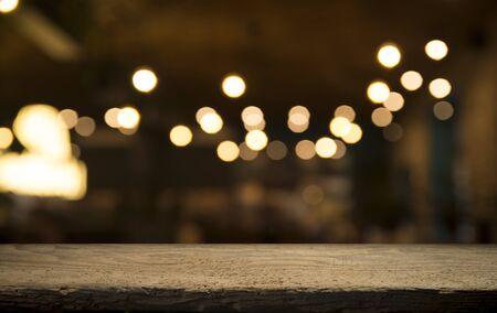Dessus de table en bois vide sur flou flou d'or clair du café-restaurant sur fond sombre.