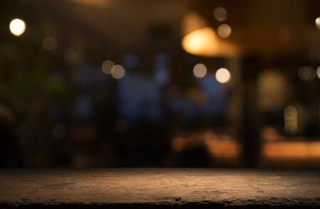 Empty wood table top on blur light gold bokeh of cafe restaurant in dark background.