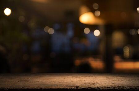 Lege houten tafelblad op vervagen licht gouden bokeh van café-restaurant op donkere achtergrond. Stockfoto