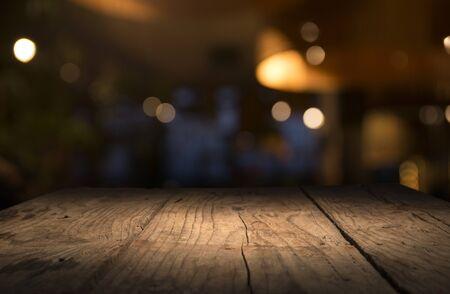 Leere Holztischplatte auf verwischen hellgoldenem Bokeh des Café-Restaurants im dunklen Hintergrund. Standard-Bild
