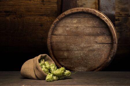 Barril de cerveza Oktoberfest y vasos de cerveza con trigo y lúpulo en la mesa de madera Foto de archivo
