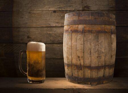 Barril de cerveza Oktoberfest y vasos de cerveza con trigo y lúpulo en la mesa de madera