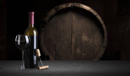 Rotwein in das Glas vor Holzhintergrund gießen