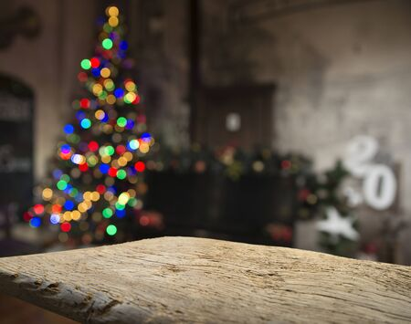 Empty table in front of christmas tree with decorations background. For product display montage.