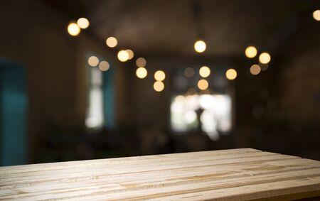 Empty wood table top on blur light gold bokeh of cafe restaurant in dark background. Stock fotó