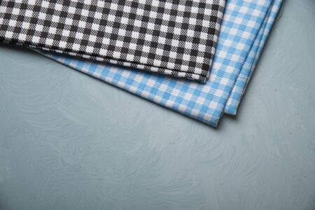 Top view of checkered kitchen tablecloth on concrete background.