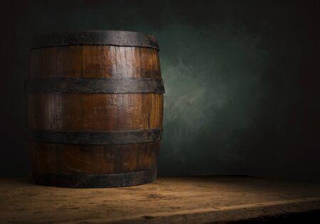 Barile di birra con bicchieri di birra su un tavolo di legno. Lo sfondo marrone scuro.