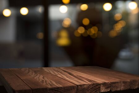 Empty brown wooden table and blur background of abstract of resturant lights people enjoy eating ,can be used for montage or display your products