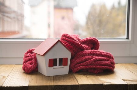 house in winter - heating system concept and cold snowy weather with model of a house wearing a knitted cap Stock Photo