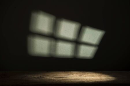 shadow of window on wall and desk of wood