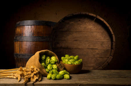 Beer. Still life with Vintage beer barrel and glass light beer. Fresh amber beer concept. Green hop and gold barley on wooden table. Ingredients for brewery. Brewing traditions Standard-Bild