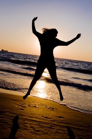 woman jumping up at beach