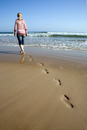 A girl leaving her footprints on the sand Stock Photo - 5122800