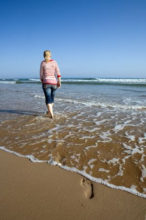 A girl walking on the beach Stock Photo - 5258620