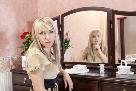 Attractive woman and her strange reflection in a mirror photo